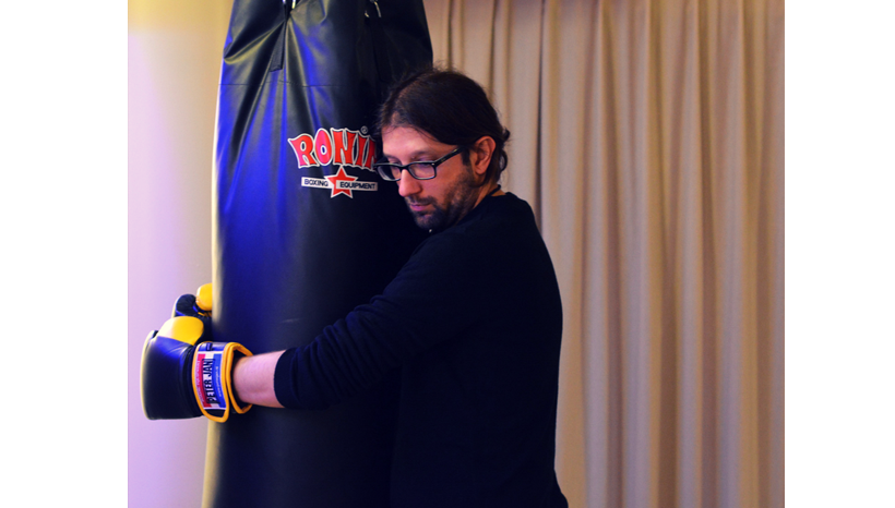 man holding punching bag during emotional release session